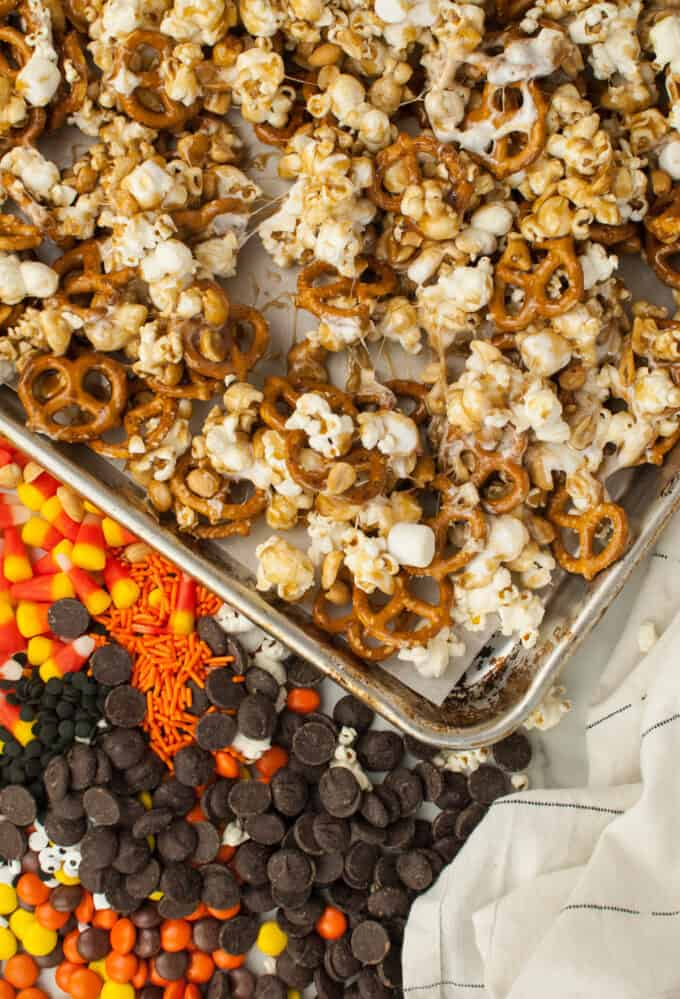 Popcorn, peanuts, and pretzels covered in sticky caramel on a baking sheet.