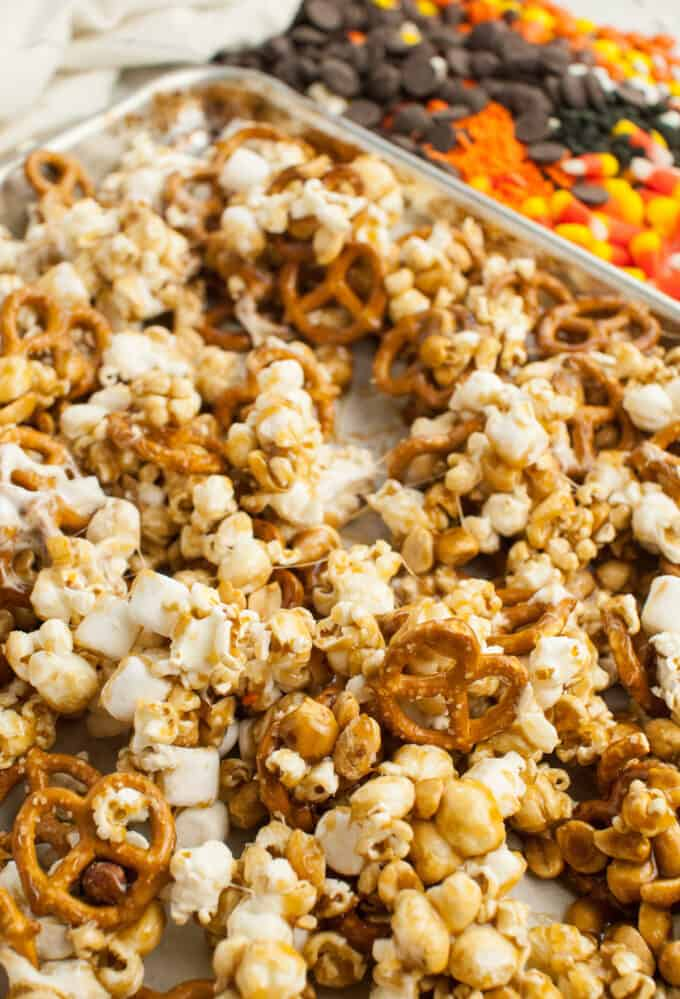 Gooey marshmallows, pretzels, popcorn, and peanuts in a caramel sauce on a baking sheet.