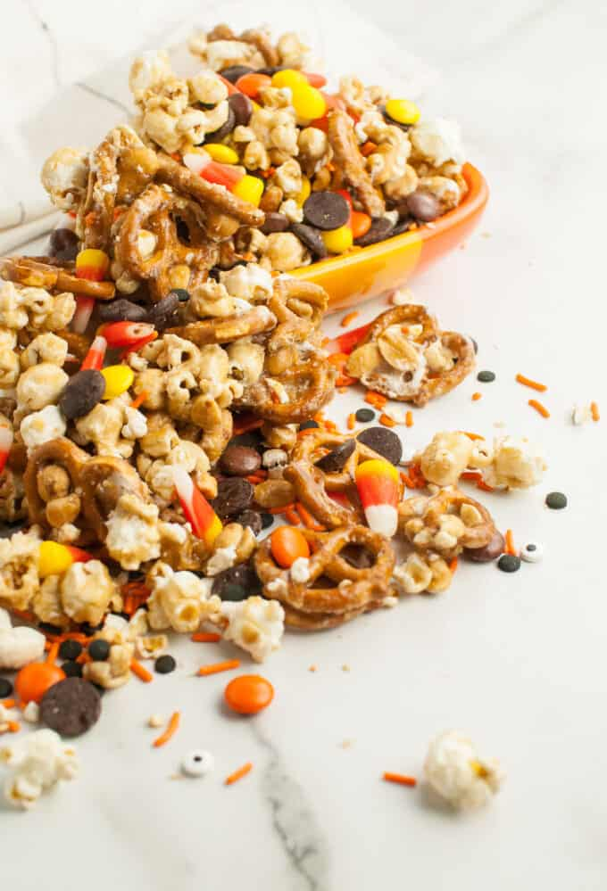Halloween caramel corn snack mix with peanut, pretzels, and M&Ms spilling out of a bowl.
