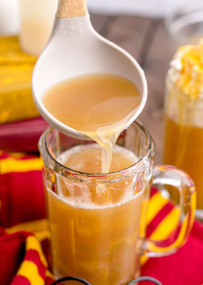 Ladling homemade butterbeer into a large glass mug.