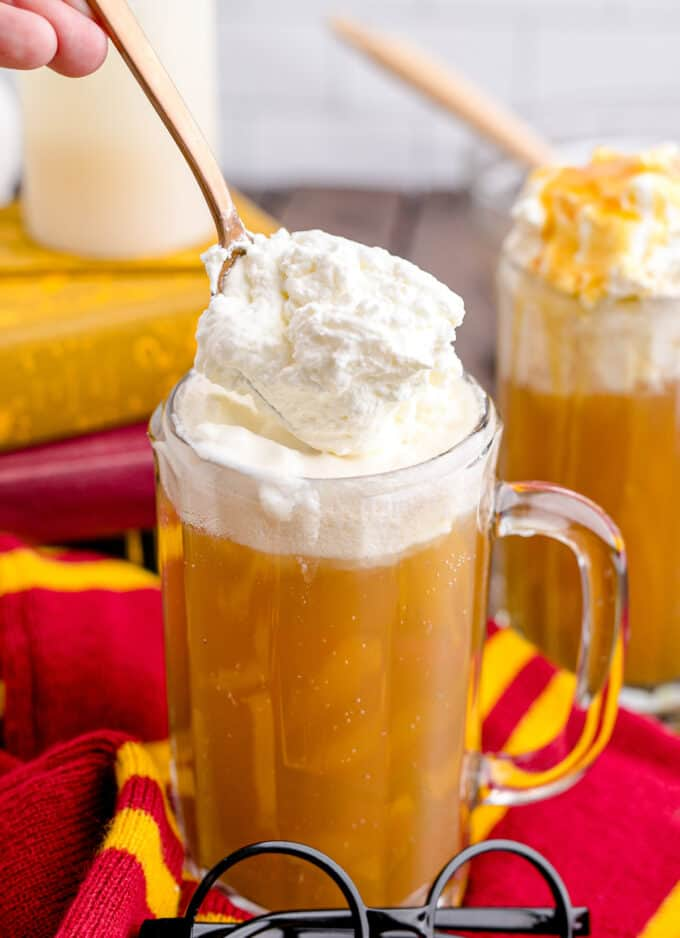 Spooning homemade whipped cream onto a mug full of Harry Potter copycat butterbeer.