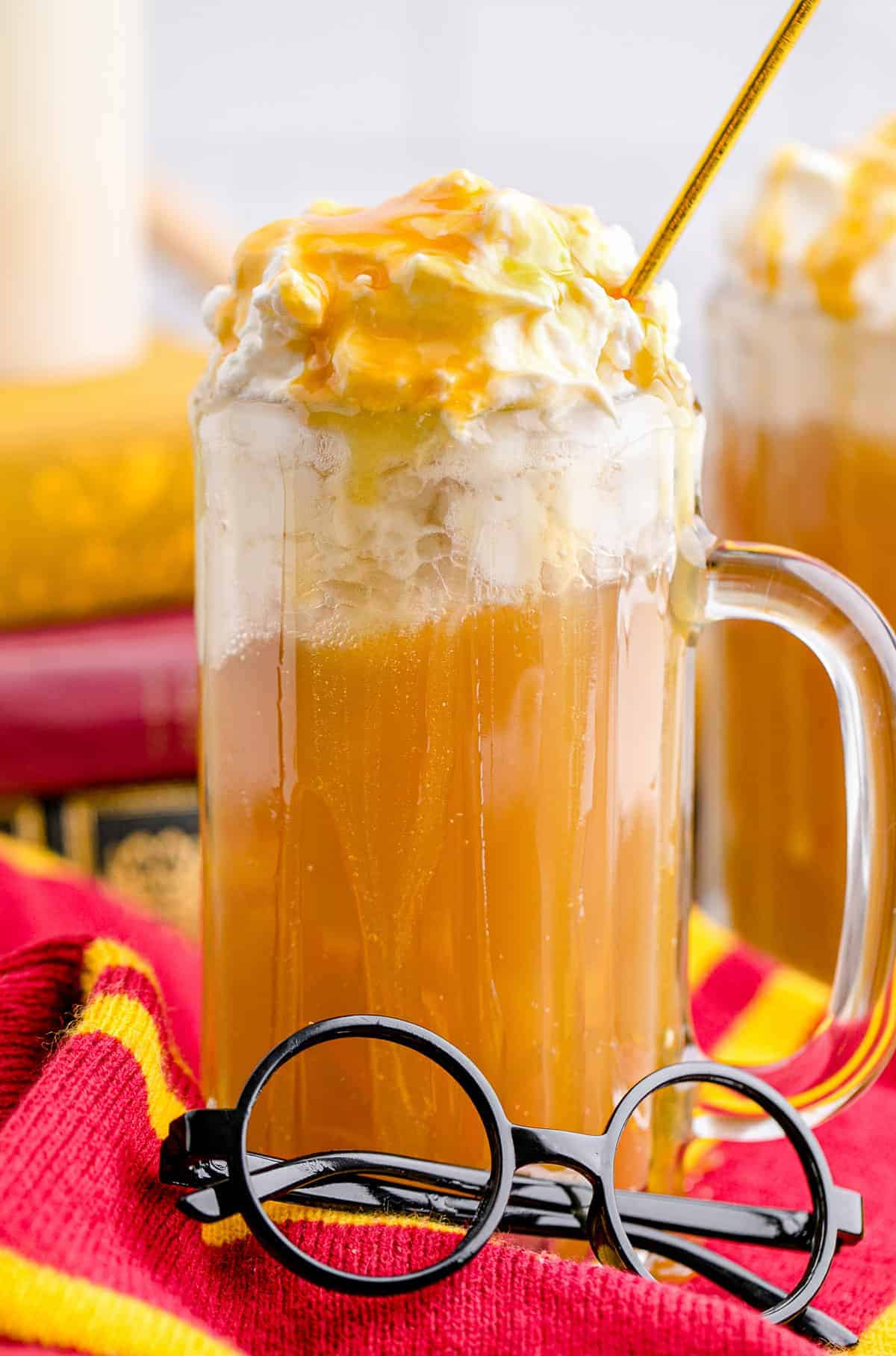 A glass mug of butterbeer with Harry Potter glasses in front of it.