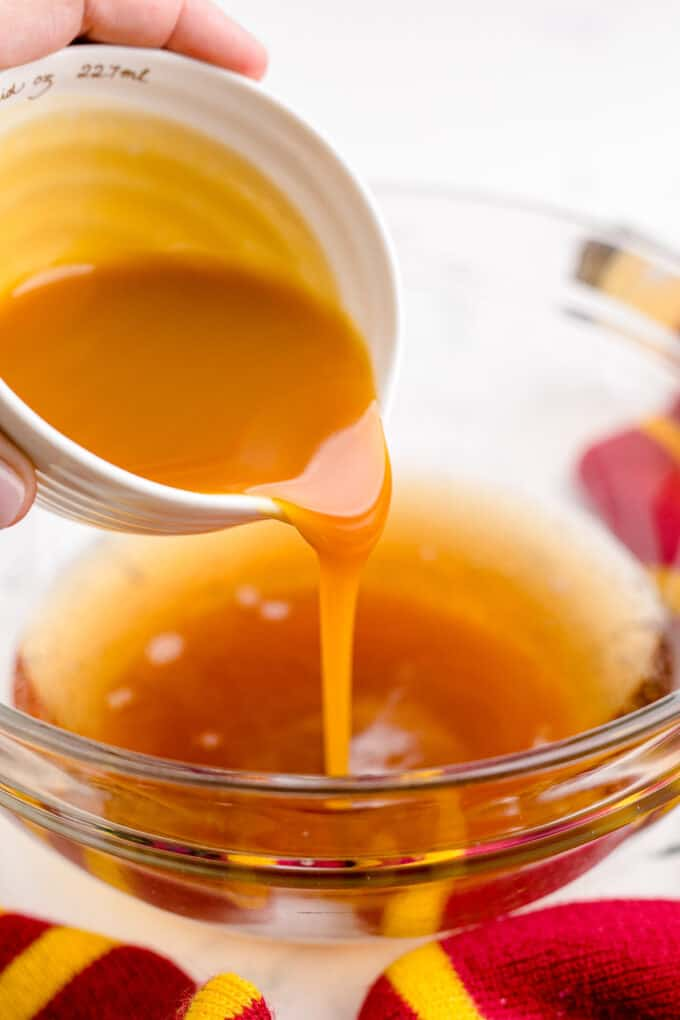 Pouring butterscotch syrup into a bowl.