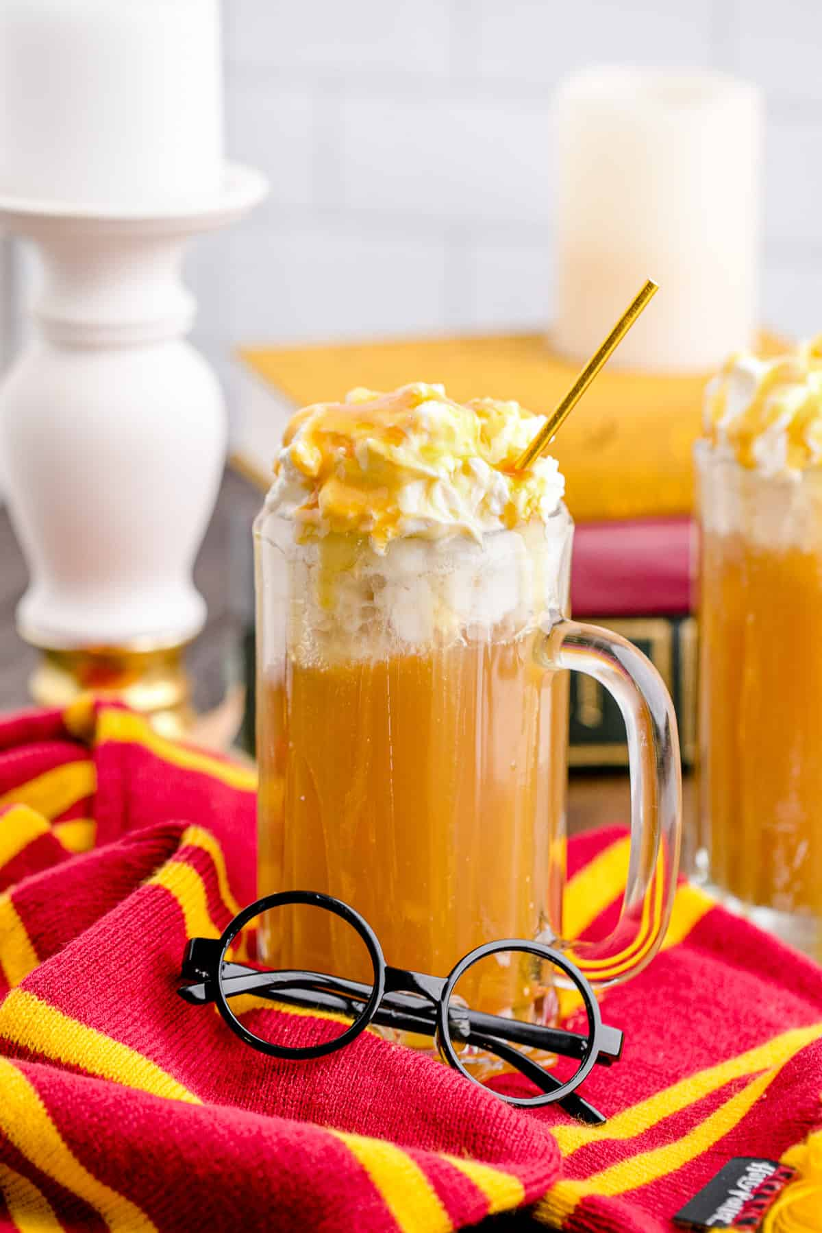 A tall mug of homemade copycat butterbeer with whipped cream and butterscotch syrup on top.