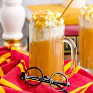 A mug of homemade butterbeer with round Harry Potter glasses in front of it.