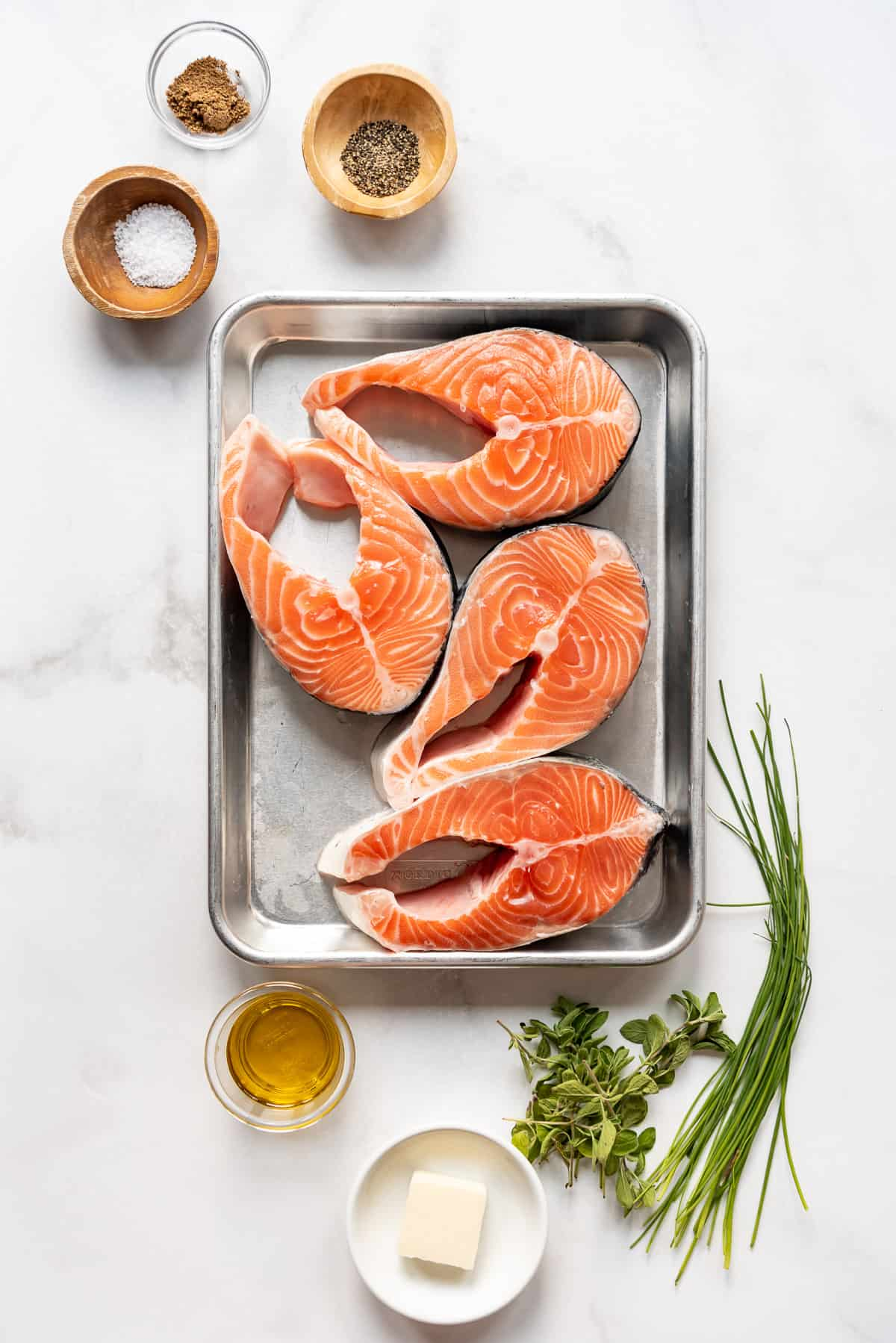 Salmon steaks on a baking sheet with salt, pepper, oil, butter, and fresh herbs around it.