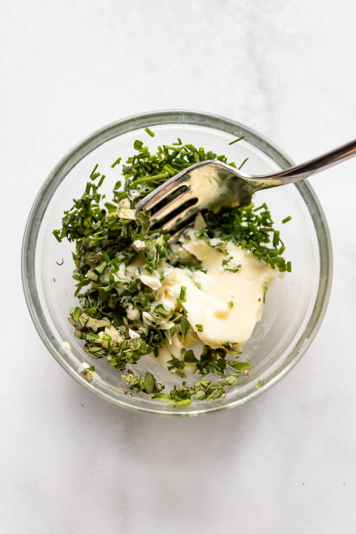 Combining butter, herbs, and garlic in a bowl with a fork.