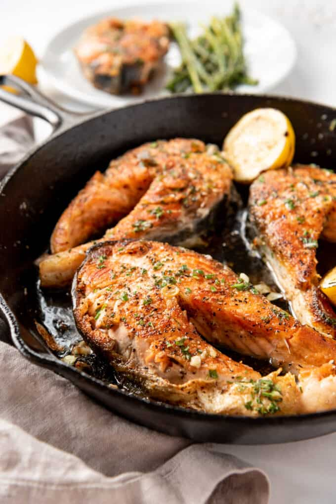 Salmon steaks that have been cooked in a cast iron pan.
