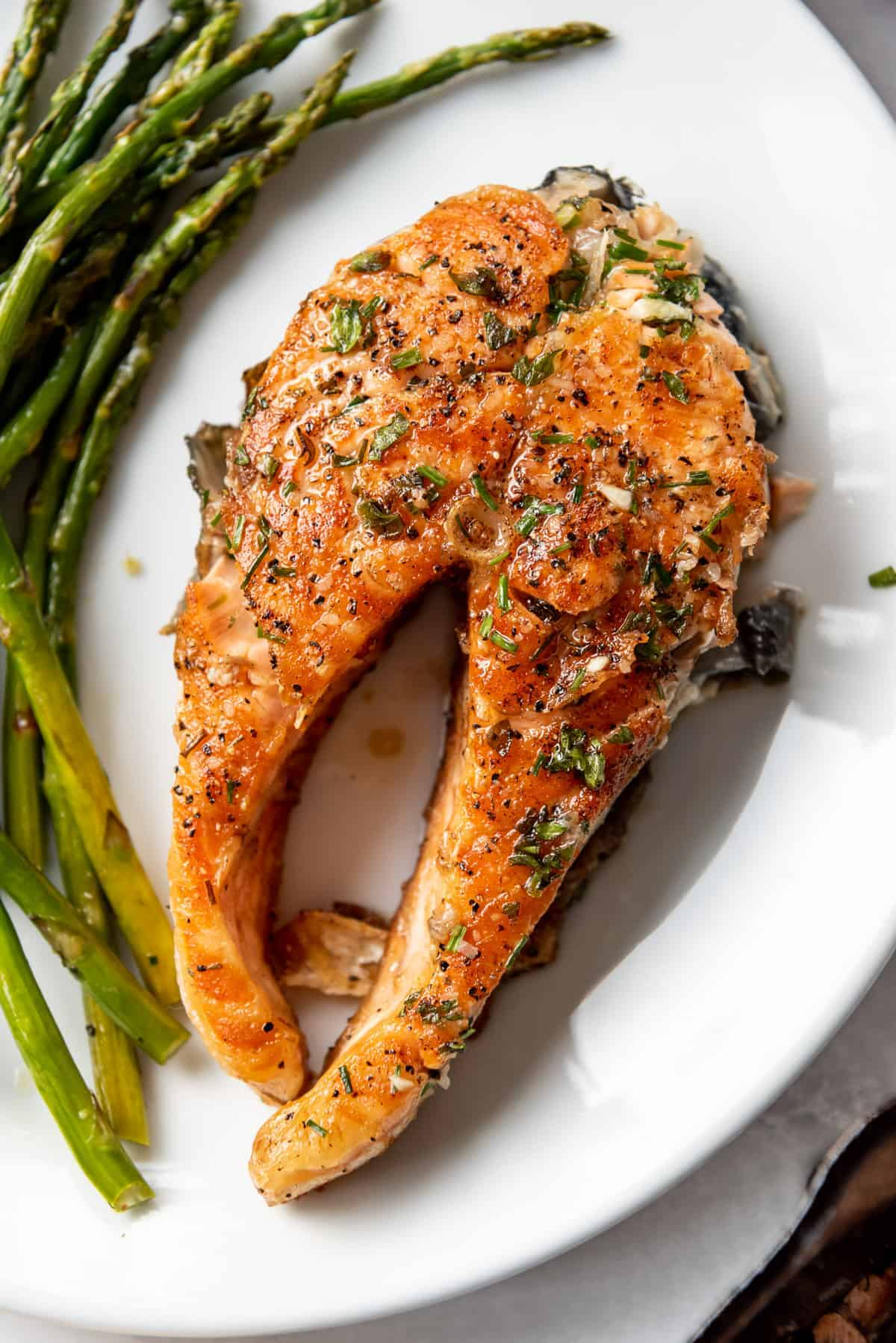 An image of a grilled salmon steak on a plate with asparagus.