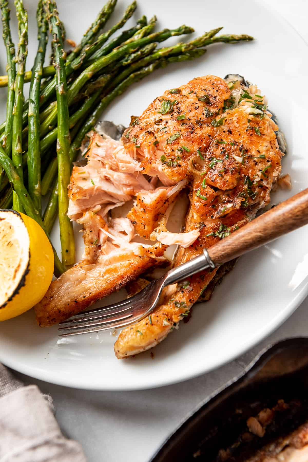 Flaked salmon on a white plate with a fork and roasted asparagus.